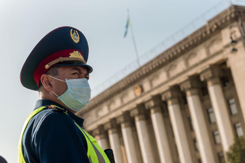 Полицейский в маске на площади Астана в Алматы