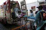 Медики в масках грузят пациента с коронавирусом в машину скорой помощи