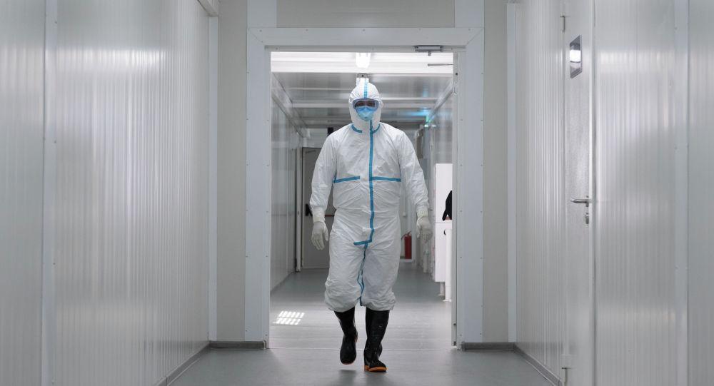 Медик в защитном костюме идет по коридору инфекционного госпиталя в Алматы