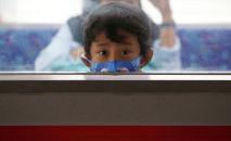 Мальчик в защитной маске выглядывает из окна пригородной электрички
