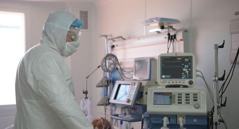 Врач работает с аппаратурой в отделении интенсивной терапии в больнице с коронавирусом в Нур-Султане