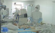 Врач в защитном костюме в палате интенсивной терапии в больнице с коронавирусом в Нур-Султане