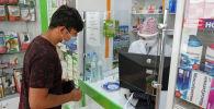 Мужчина в маске покупает лекарства в аптеке