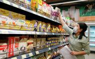 Сотрудница магазина в маске расставляет продукты на полки