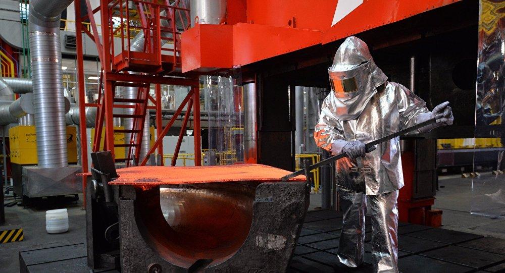 Архивное фото рабочего , устанавливающего заготовку для изделия в пресс на заводе