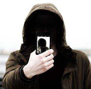 Человек в капюшоне с телефоном в руке