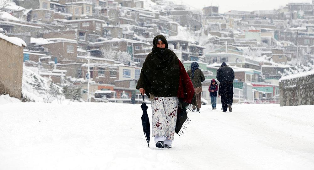 Афганская женщина идет по заснеженному Кабулу, Афганистан, 5 февраля 2017 год