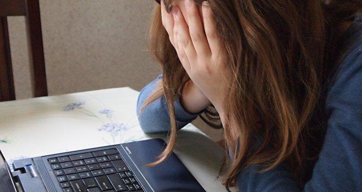 Девочка-подросток сидит перед компьютером, закрыв лицо руками