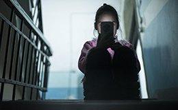 Девочка с мобильным телефоном в руках сидит на лестничной площадке