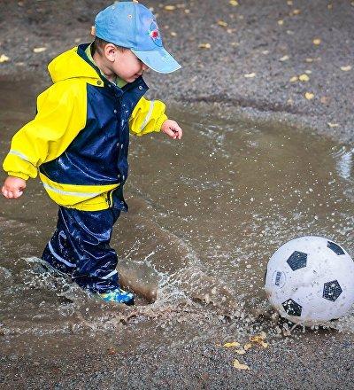 Ребенок играет в мяч после дождя.