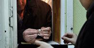 Ломбардқа зергерлік бұйым өткізіп жатқан ер адам, архивтегі сурет