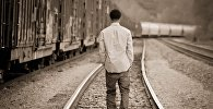 Мужчина шагает по железнодорожным путям