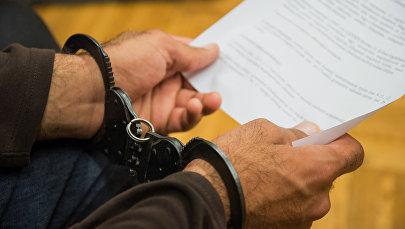 Человек в наручниках держит официальный документ, фото из архива