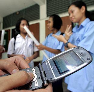 Школьники с мобильными телефонами