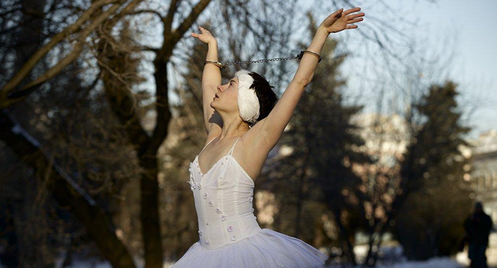 Архивное фото балерины, участвующей в акции протеста против нарушений прав человека, танцующей на снегу в наручниках