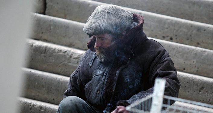 Бездомный курит на лестнице, фото из архива
