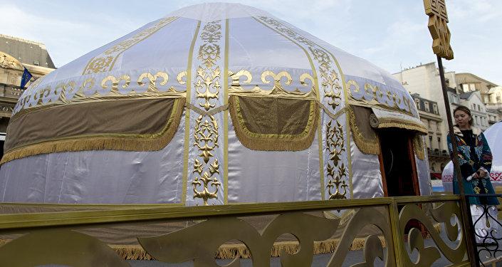 Женщина в казахской национальной одежде стоит возле юрты во время праздничного мероприятия, архивное фото