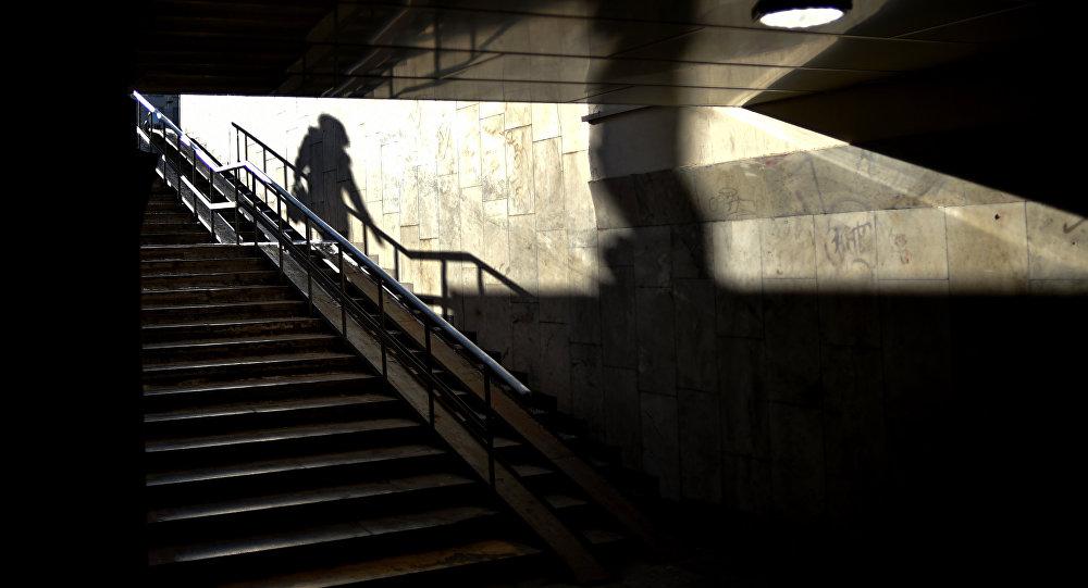 Тень женщины, спускающейся в подземный переход