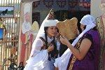 Девушка в казахском национальном костюме смотрит в зеркало