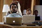 Компьютермен жұмыс істеп отырған адамдар