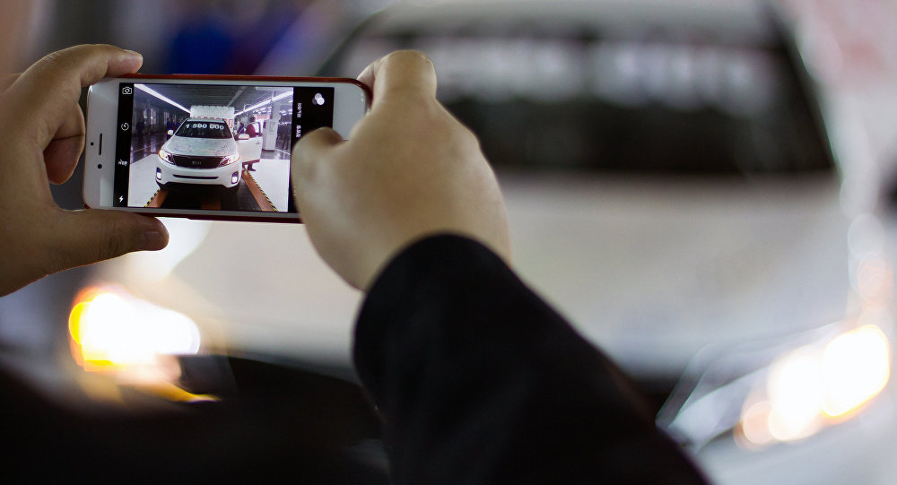 Человек фотографирует автомобиль