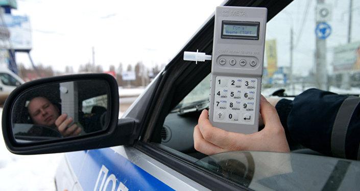 Полицейский держит в руках алкотестер