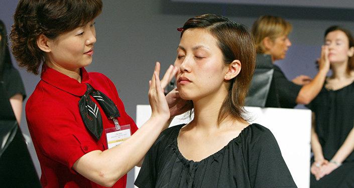 Косметолог наносит омоложивающий крем на кожу девушки-модели, архивное фото