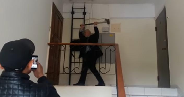 Частный судебный исполнитель Р.Жилкибаев выбивает двери кувалдой в Астане