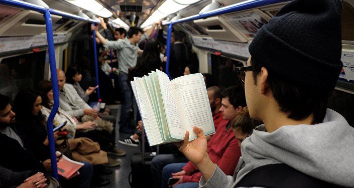 Молодой человек читает книгу в метро