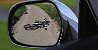 Велосипед на дороге отражается в боковом зеркале автомобиля
