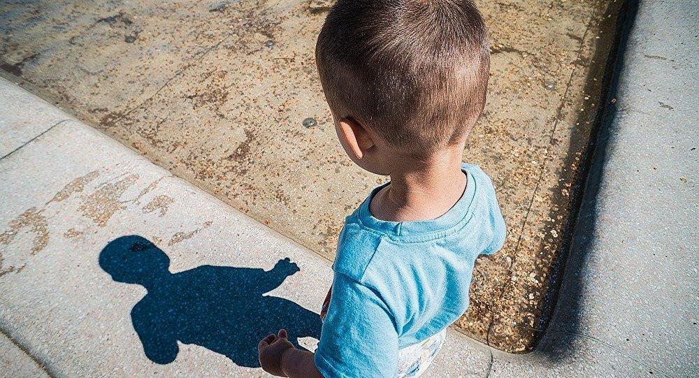 Ребенок смотрит на свою тень, архивное фото