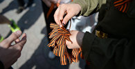 Волонтер раздает георгиевские ленточки, архивное фото