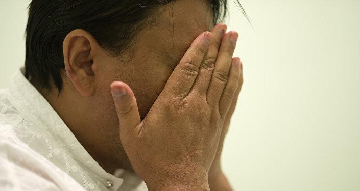 Архивное фото мужчины, закрывшего лицо руками