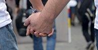 Мужчины держатся за руки, архивное фото
