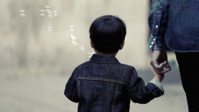Мальчик держит мужчину за руку