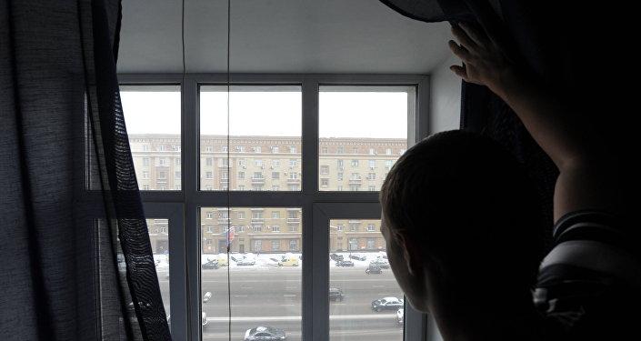 Мужчина смотрит из окна на улицу