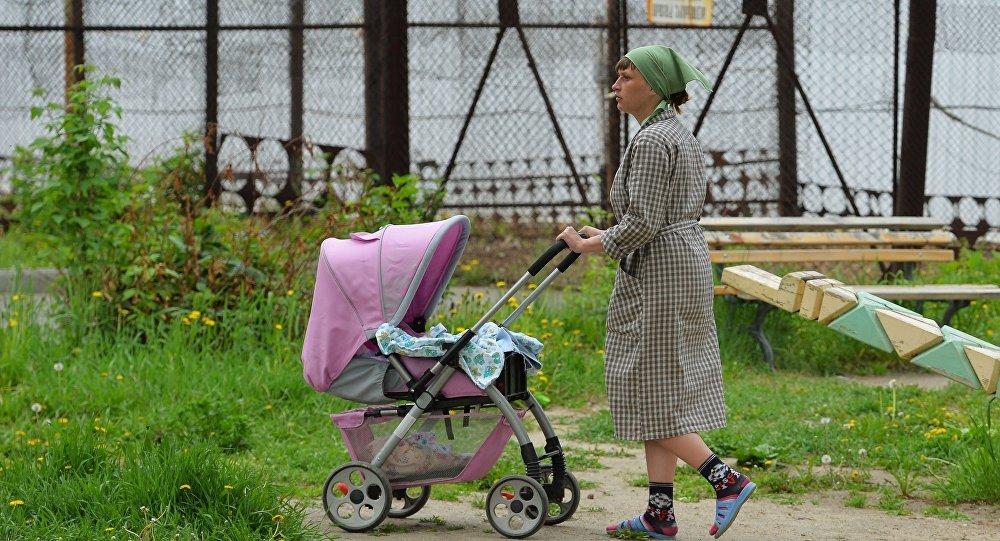 Архивное фото заключенной, гуляющей с ребенком по площадке Дома ребенка на территории колонии