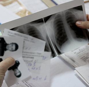 Врач изучает документы пациента во время медицинского осмотра, архивное фото