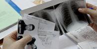 Дәрігер медициналық тексерістен өткен науқастың құжаттарын қарап жатыр, архивтегі фото