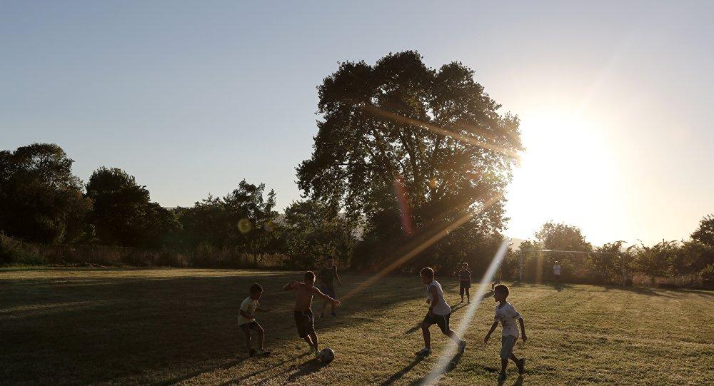 Дети играют летом в футбол, архивное фото
