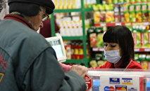 Продавец в супермаркете на фоне прилавка с соком