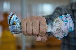 Деньги в кулаке, архивное фото