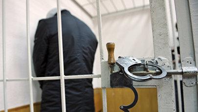 Архивное фото человека в клетке для подсудимых