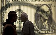 Прохожие на фоне постера с изображением доллара