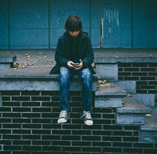 Подросток с сотовым телефоном, иллюстративное фото