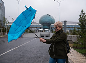Девушка с зонтом в ветренную погоду на фоне главного павильона ЭКСПО-2017 в Астане