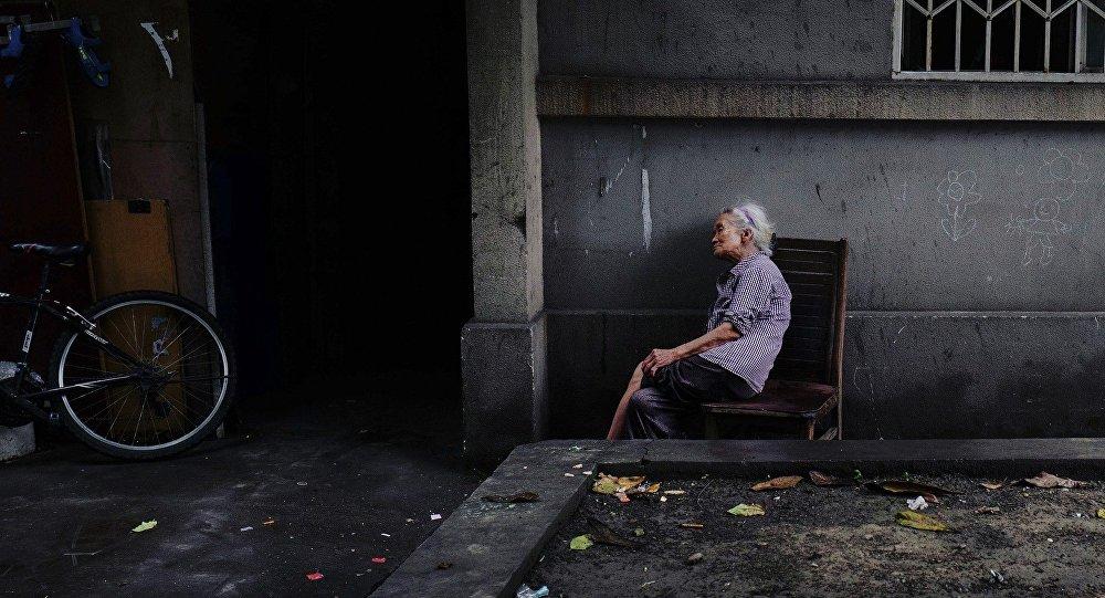 Пожилая женщина у подъезда дома