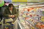 Женщина изучает ценник на продуктах