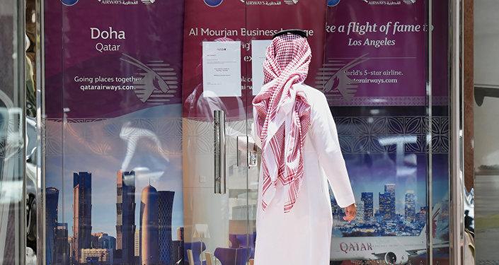 Человек рассматривает вывеску офиса Qatar Airways в столице Саудовской Аравии Эр - Рияде, архивное фото
