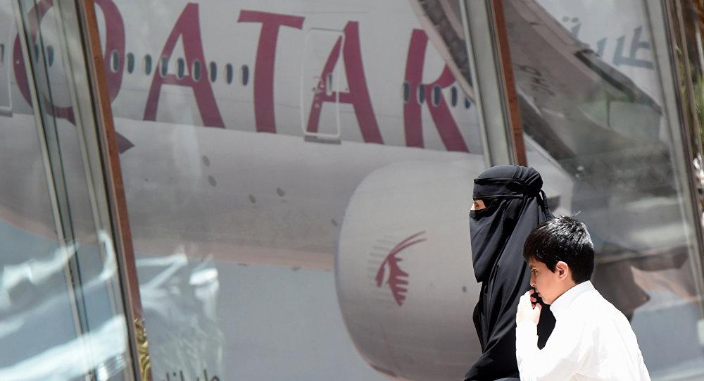 Женщина и мальчик идут мимо офиса Qatar Airways в столице Саудовской Аравии Эр - Рияде, архивное фото